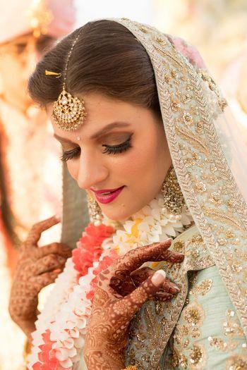 Photo of Bride in light blue lehenga with brown smokey eye