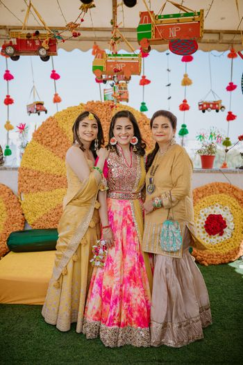 Bride posing with her mother and sister on her Haldi.