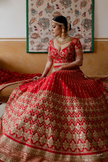 bride in a red and gold lehenga getting ready shot