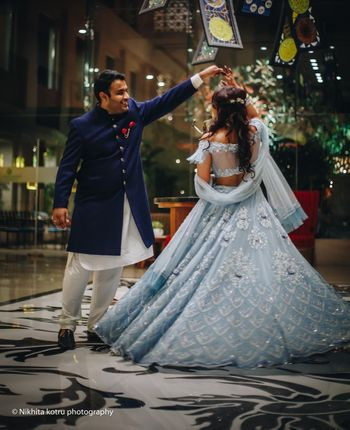 Photo of Twirling bride and groom in shades of blue