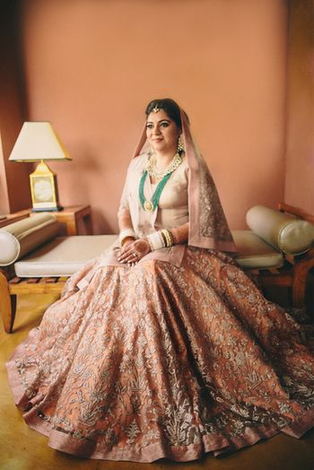 Photo of elegant pastel peach bridal lehenga with long top