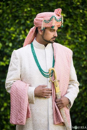 Groom in white sherwani with pink turban and green beads
