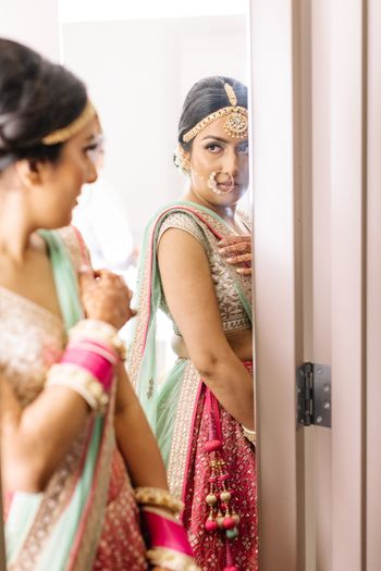 Photo of Bride getting ready shot while looking into mirror