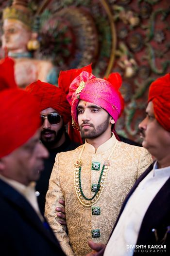 Beige and gold groom sherwani with green buttons