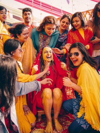 Bridesmaids applying haldi on the bride.