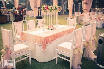 Photo of White and peach reception table seating with florals