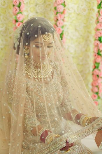 Bride in light peach lehenga holding dupatta as veil