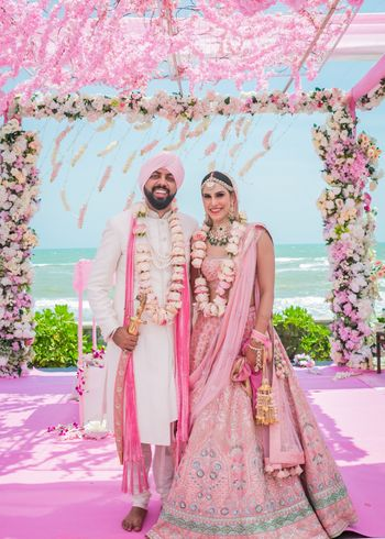 Just married, the couple in coordinated outfits in shades of pink and white!
