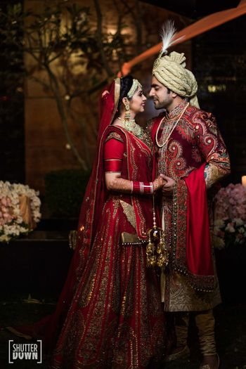 Photo of Traditional bride and groom in maroon outfits