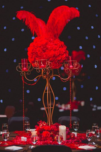 Photo of black and red table centerpieces for sangeet moulin rouge theme