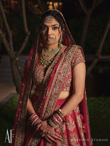 Photo of Bride looking regal in silver jewellery and red lehenga