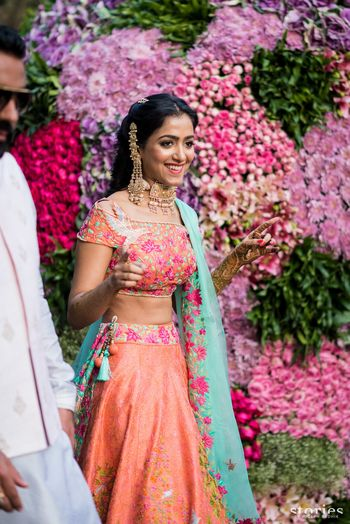 Photo of Mehendi bridal look in peach lehenga with unique earrings