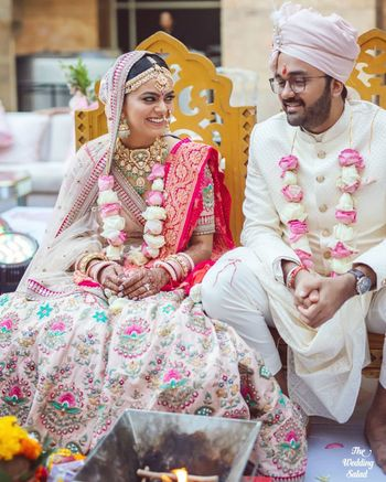 Photo of cute couple photo with the bride in a pastel pink sabyasachi lehenga