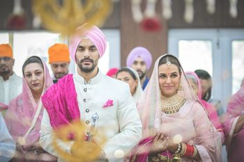 Celebrity couple Neha Dhupia and Angad Bediin color coordinated outfits at their anand karaj ceremony