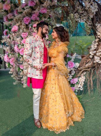 Photo of Mehendi couple portrait with groom in bright outfit and bride in yellow lehenga