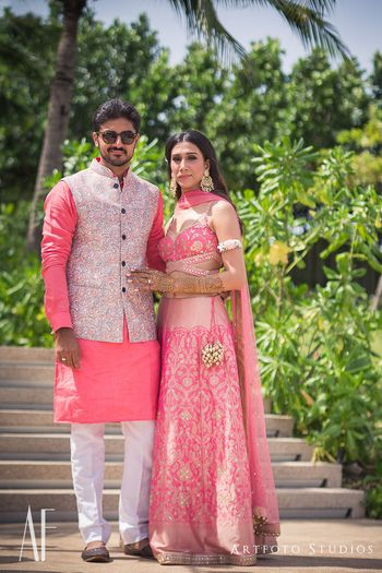 Matching bride and groom in coral outfits for mehendi