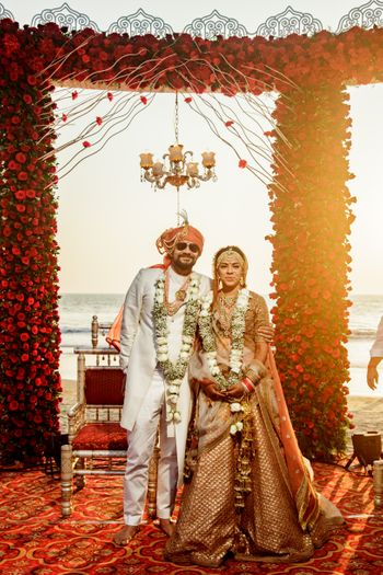 Photo of matching bride and groom with orange and white outfits and beachside mandap