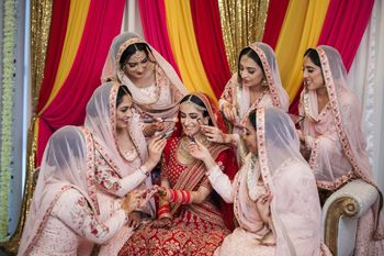 Photo of Bride posing with her bridesmaids on her wedding day.