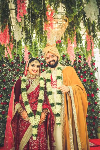 Photo of Candid couple  shot with bride in a red saree