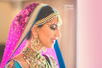 Photo of matha patti and earrings and bridal necklace with green enamel worn with pink dupatta and flowers in hair