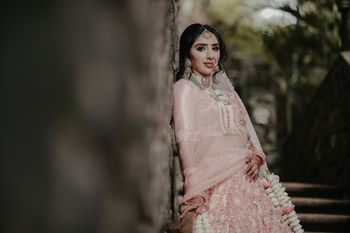 bridal portrait with floral kaleere and green jewellery with pastel lehenga