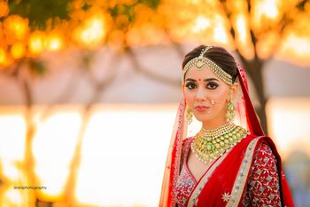 Photo of Bridal portrait with contrasting jewellery and red lehenga