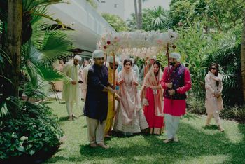 A bridal entry with the bride in a pink lehega, and under the phoolon ki chaadar!