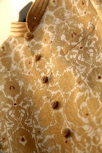 Photo of brocade sherwani in gold and white with gold buttons