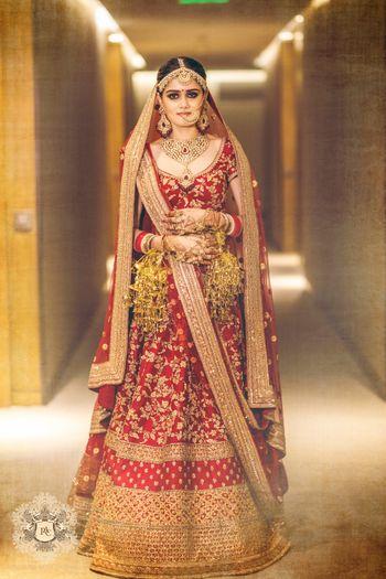 Red and gold bridal lehenga wearing kaleere