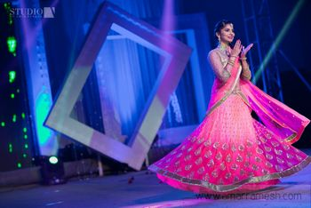 Photo of bright pink flowy sangeet lehenga with gold blouse