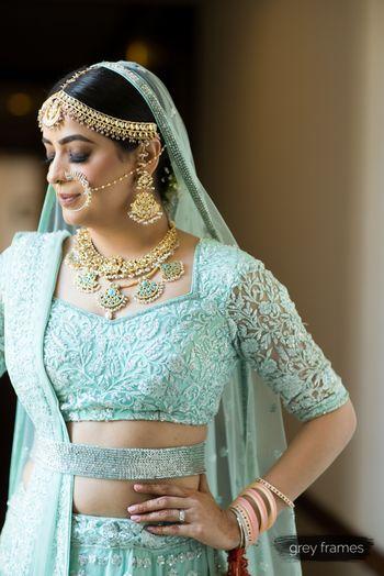 Beautiful bride in aqua blue lehenga with gold jewellery