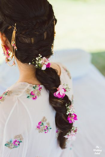 pretty mehendi braided hairstyle with flowers and babys breath