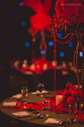 black and red table centerpieces for sangeet moulin rouge theme