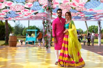 A color-coordinated couple in bright outfits for their day mehndi ceremony
