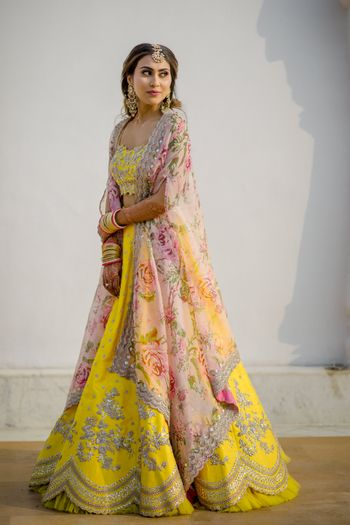 Bride wearing a yellow lehenga with a floral print dupatta