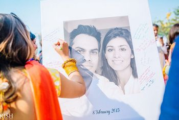 Photo of Guests sign and leave messages on a guest book which is a printed photo of the bride and groom