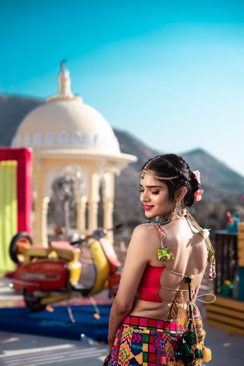 Photo of A backless blouse worn with a milticoloured mehendi lehenga