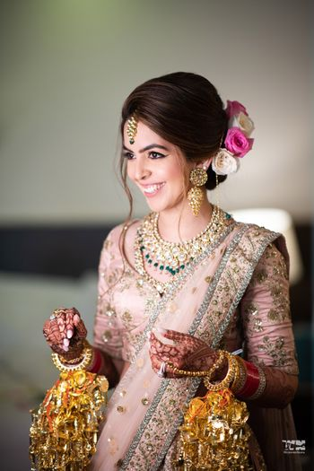 Photo of A bride in a blush pink lehenga and gold jewelry smiling for the camera