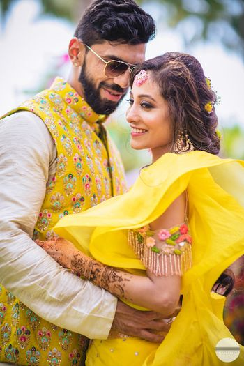 A bride and groom pose on their mehendi