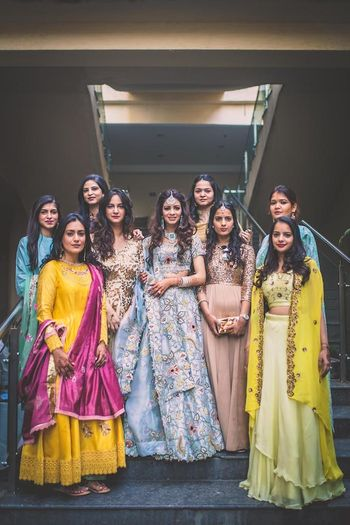 A bride poses with her bridesmaids in blue lehenga