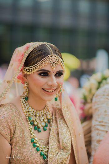 Pretty bridal portrait in peach lehenga and green jewellery