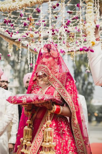 A  sikh bride in a pink lehenga enters under a phoolon ki chaadar
