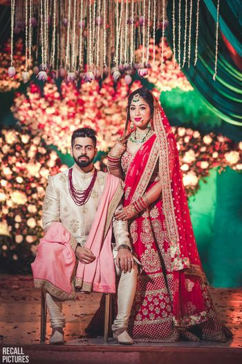 Groom in white and bride in red lehenga
