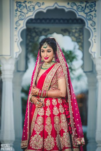 Photo of Bride in red classic lehenga with green jewellery