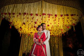 Wedding day couple shot against floral mandap