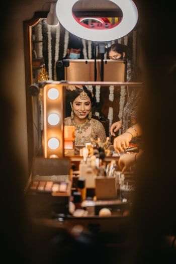 Bride looks at herself in mirror while getting ready