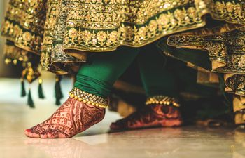 Photo of bridal payal or pajeb with green anarkali