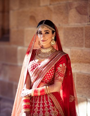 Photo of A bride dressed in a red Sabyasachi lehenga on her wedding day