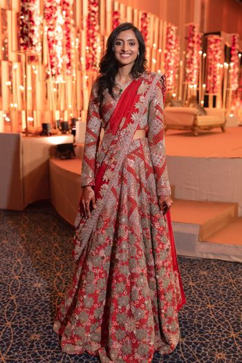 A happy bride dressed in red lehenga at her wedding function