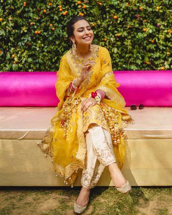 Bride in a yellow kurta for her mehendi
